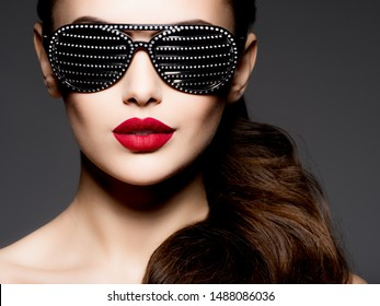 Fashion portrait of  woman wearing black sunglasses with diamonds and red lips