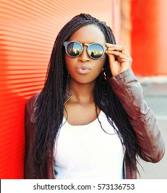 Fashion portrait young african woman in black sunglasses at city over red background