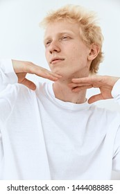 Fashion portrait of Young albino guy model with blonde hair posing and gesture against white background