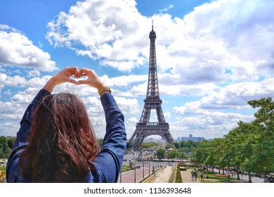 Fashion Portrait of young Asian girl in hand heart sign with jean shirt in summer vacation.Brightness style tone colour on beautiful sky and Eiffel Tower in background at Paris,France.