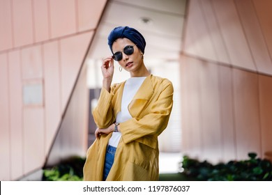 A fashion portrait of a young and attractive Muslim Malay woman in the city. She is well-dressed and fashionable with a navy turban (hijab head scarf) and sunglasses; she is posing for her photograph.