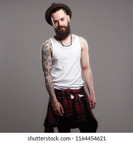 fashion Portrait of young bearded man. Smiling Hipster boy. handsome man in hat. Brutal bearded boy with tattoo