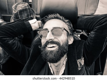 Fashion portrait of young bearded man ready for road trip - Cheerful hipster guy sitting in car looking the sky - Black and white editing - Warm vintage retro filter