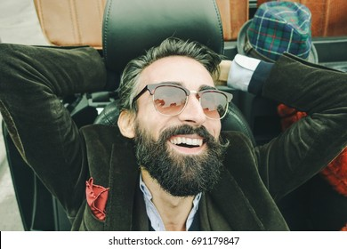Fashion portrait of young bearded man ready for road trip - Cheerful hipster guy sitting in car looking the sky - Focus on beard and sunglasses - Trendy lifestyle concept - Vintage retro filter