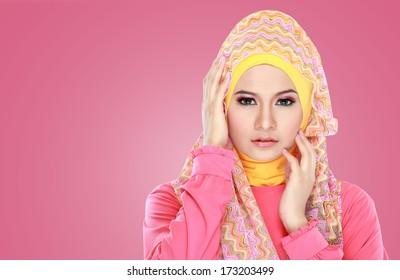 Fashion portrait of young beautiful asian muslim woman with pink costume wearing hijab