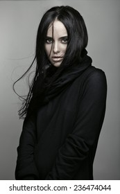 Fashion portrait of a young beautiful brunette girl with long black straight flying hair. Magnificent hair. Black roll neck jumper.