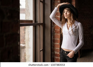 fashion portrait of young beautiful confident woman wearing hat, posing in at the window