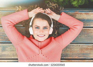 fashion portrait of young beautiful, fashionable, curly girl in headphones. color of the year 2019 Living coral