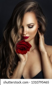 Fashion portrait of young beautiful lady with red rose on black background