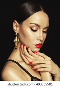 Fashion portrait of young beautiful lady with earring on black background