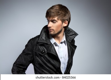 Fashion portrait of the young beautiful man over gray background