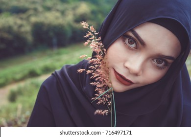 Fashion portrait of young beautiful muslim woman with the black hijab.Muslim woman holding grass flower.Vintage style