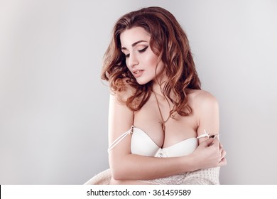 Fashion portrait of young beautiful sexy woman with long wavy hair. Pretty girl sitting in white bra or lingerie in studio. Fashion style toned colors portrait