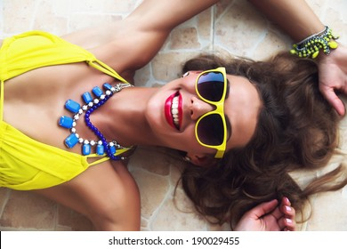 Fashion portrait of young beautiful woman lying on the floor, wearing bright sunglasses bikini and jewelry, laughing and have summer mood.