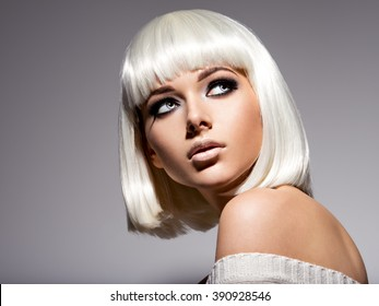 Fashion portrait of young beautiful woman with hairstyle bob and black makeup of eye