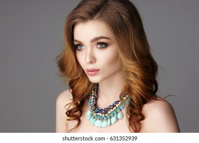 Fashion portrait of young beautiful woman with jewelry. Red hair girl. Perfect makeup. Beauty style girl with accessories