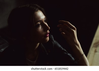 Fashion portrait of young beautiful woman with deep shadows, female isolated close-up, dramatic and sad. Profile of a girl in dark background.