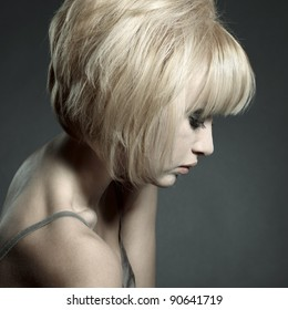 Fashion portrait of young beautiful woman with blond hair looking down sadly