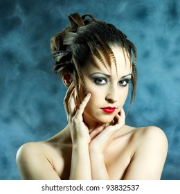 Fashion portrait of young beautiful woman with brunette fashion styled hair looking in camera posing in smoke
