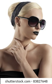 fashion portrait of young blond woman with hair style black lips and wearing sunglasses posing against white background