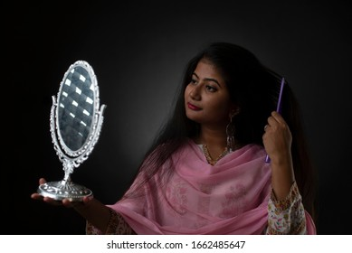 Fashion portrait of young brunette Indian Bengali woman with traditional wear combing her hair in front of a mirror in black studio copy space background. Indian lifestyle.
