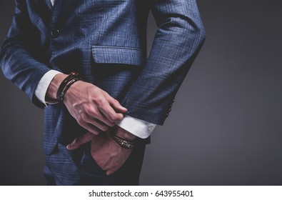 Fashion portrait of young businessman handsome model man dressed in elegant blue suit with accessories on hands posing on gray background in studio. Hands in pockets