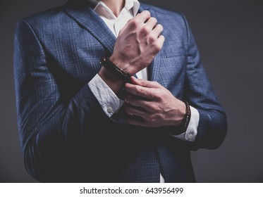 Fashion portrait of young businessman handsome model man dressed in elegant blue suit with accessories on hands posing on gray background in studio. Buttoning his jacket