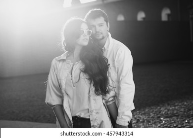 Fashion portrait of young couple in love posing at street. Beautiful girl and handsome boy hugging outdoors at sunset