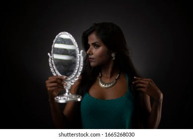 Fashion portrait of young dark skinned Indian/African brunette girl in green western dress looking at the mirror in front of black copy space studio background. Indian fashion photography.