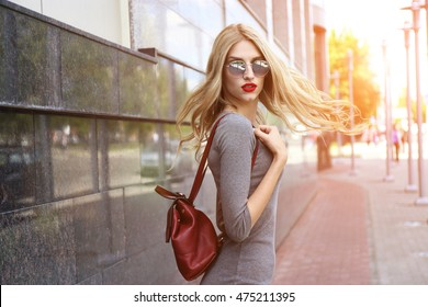 Fashion portrait of young elegant blond woman outdoor. Grey dress, leather backpack, sunglasses