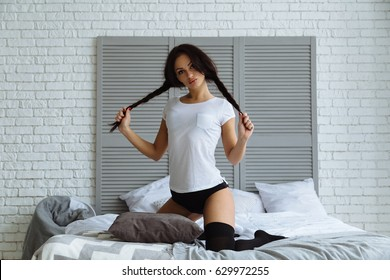 Fashion portrait of young elegant sexy woman in bed at morning