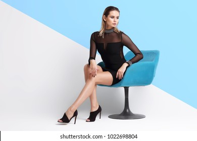 Fashion portrait of young elegant woman. Black short dress, sitting in armchair, isolated studio shot