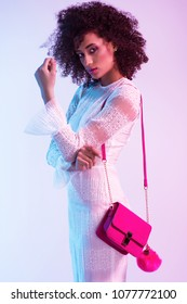 Fashion portrait of young elegant woman in nice clothes. Colored background, neon lights, studio shot. Amazing afro hair