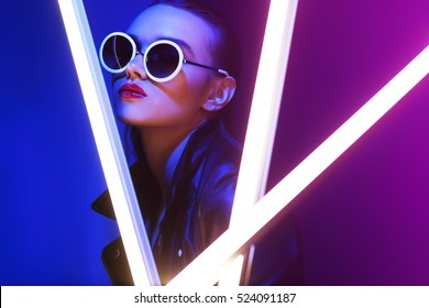 Fashion portrait of young elegant woman in sunglasses. Colored background, studio shot