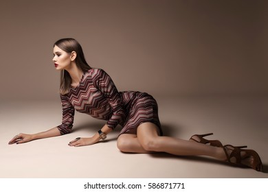 Fashion portrait of young elegant woman in studio. Brown background