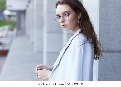 fashion portrait of young elegant woman outdoor in jacket, dress, glasses. Trendy fashion look