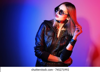 Fashion portrait of young elegant woman in sunglasses. Black leather jacket, colored background, studio shot