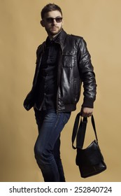 Fashion portrait of young handsome man model in leather jacket holding leather bag, wearing trendy sunglasses and poses over beige background. Close up. Copy-space.