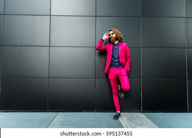 Fashion portrait of a young hipster man walking outdoors with a red formal suit - Unusual businessman going to work