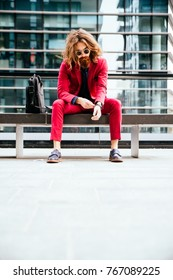 Fashion portrait of a young hipster man sitting on a bench outdoors with a red formal suit - Unusual businessman going to work