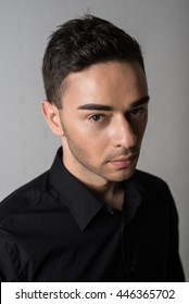 Fashion portrait of young man in black shirt poses over wall