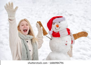 Fashion portrait of young model girl indoors with Christmas snowman. Happy girl playing with a snowman on a snowy winter walk