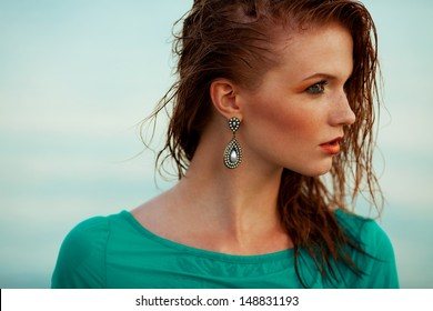 Fashion portrait of a young model with wet long ginger (red) hair in blue dress posing at the seaside. Perfect skin and make-up. Profile. Close up. Copy-space. Outdoor shot