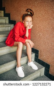 Fashion portrait of young preteen girl wearing red dress and white sneakers, spiral rubber band, sitting on the stairs