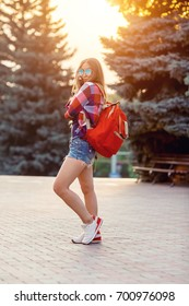 Fashion portrait of young pretty hipster woman outdoor with long hair and red backpack in the sunny summer street. The evening sunset over the city.