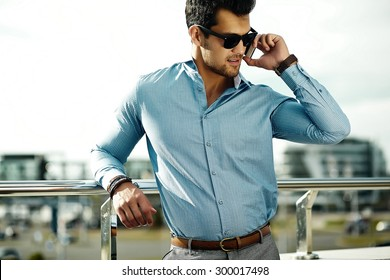 Fashion portrait of young sexy businessman handsome  model man in casual cloth suit in sunglasses in the street speaking on his phone