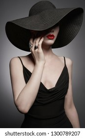 Fashion portrait of young sexy lady with beautiful black hat and evening dress. Stylish elegant woman with modern jewelry. Studio photo of pretty model on grey background.