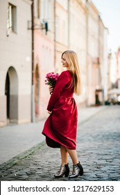Fashion portrait of young stylish lady woman with bouquet of flowers walking on the street, wearing cute trendy outfit, beautiful girl in a red dress smiling enjoy her weekends.