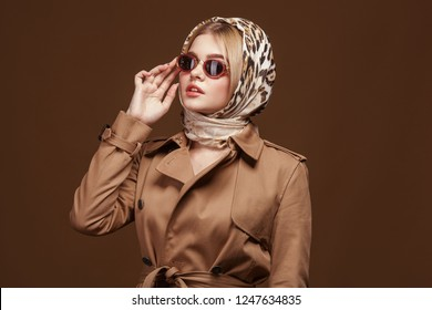 Fashion portrait of young stylish woman in trendy trench coat, leopard print headdress and fashion sunglasses over beige background.