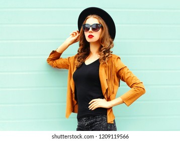 Fashion portrait young woman in black round hat, sunglasses posing on gray wall background